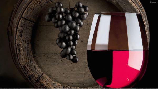 Red Wine Glass N Hanging Black Grapes Closeup
